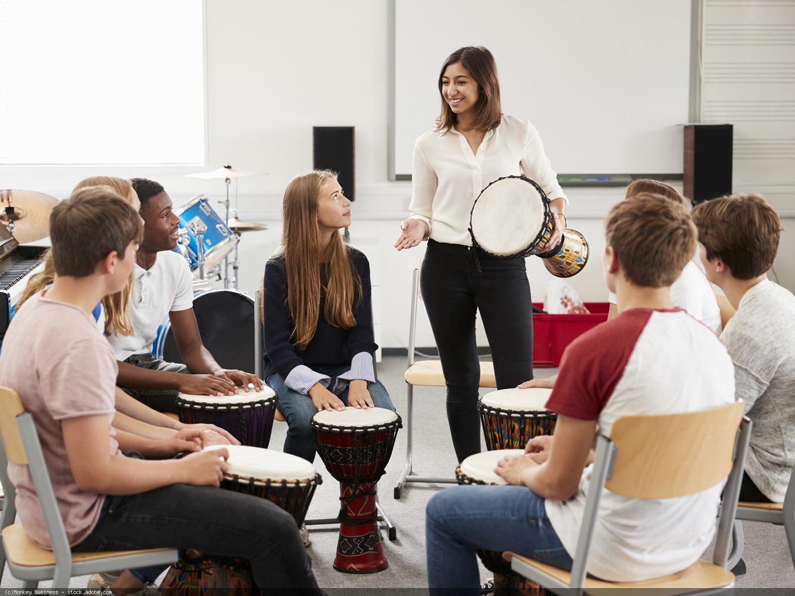 Schülerinnen und Schüler lernen in der Gruppe ein Percussioninstrument