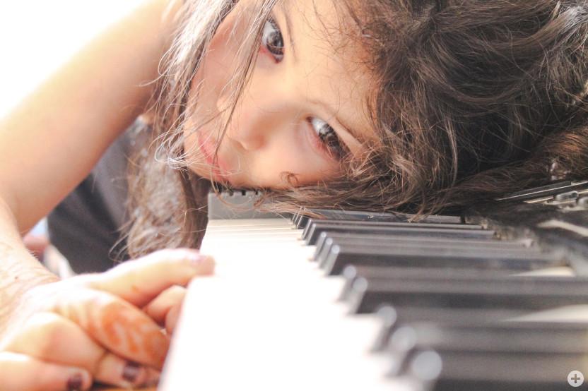 Mädchen über Klaviertastatur gebeugt